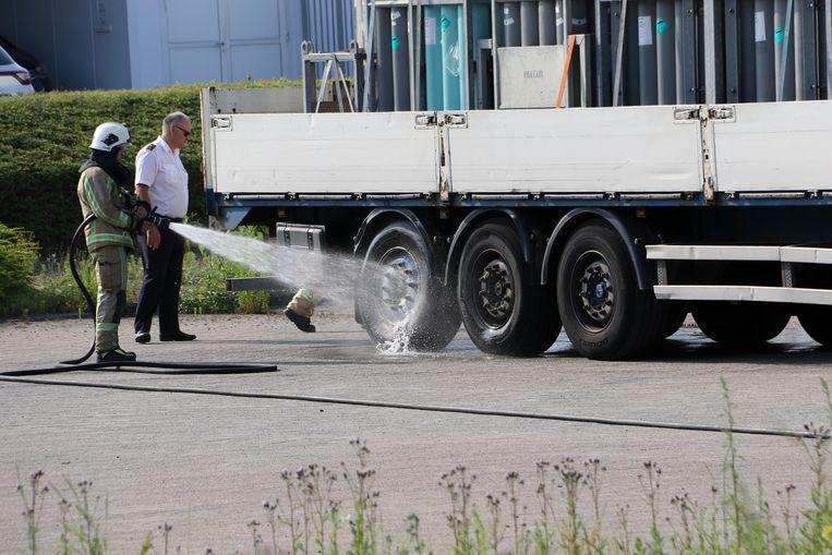 De brandweer koelt het oververhitte achterwiel af. De trailer was geladen met zuurstofflessen.