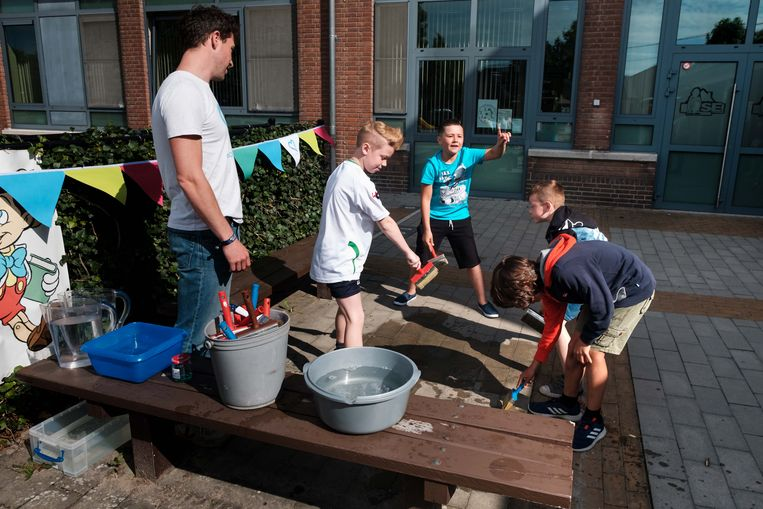 De kinderen spelen spelletjes met water