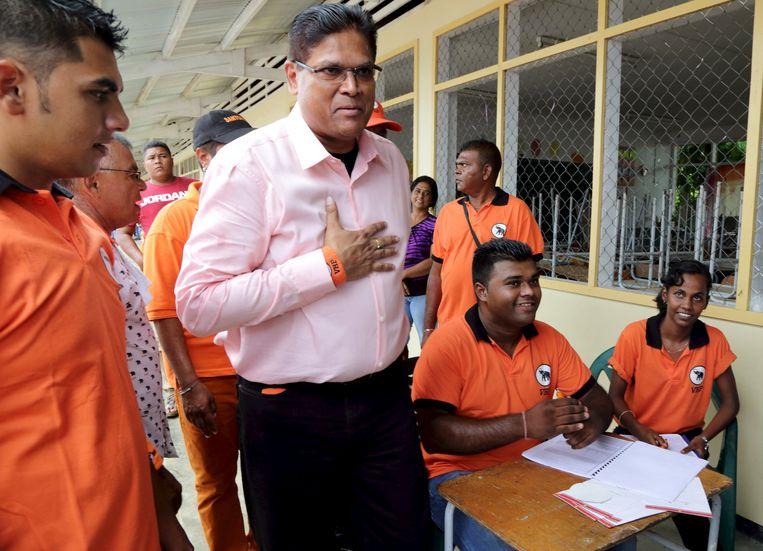 Oppositie-leider Chan Santokhi groet aanhangers bij een stembureau in Paramaribo. Beeld reuters