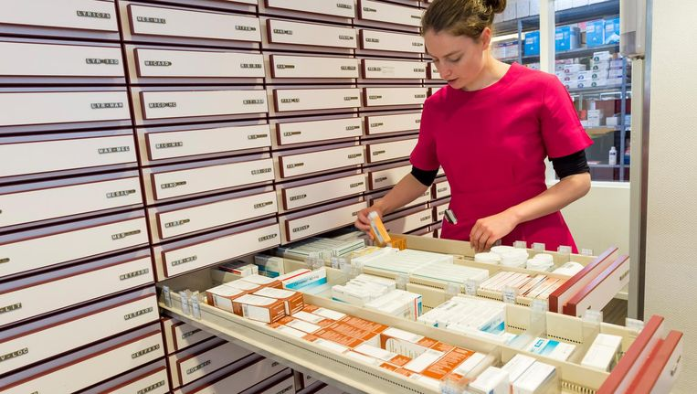 Een apothekersassistente zoekt medicijnen bij elkaar Beeld anp