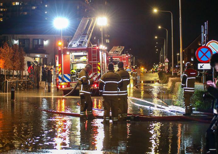 Brandweerlieden proberen wateroverlast op de Langeweg tussen Zwijndrecht en Hendrik-Ido-Ambacht te beperken door water weg te pompen.