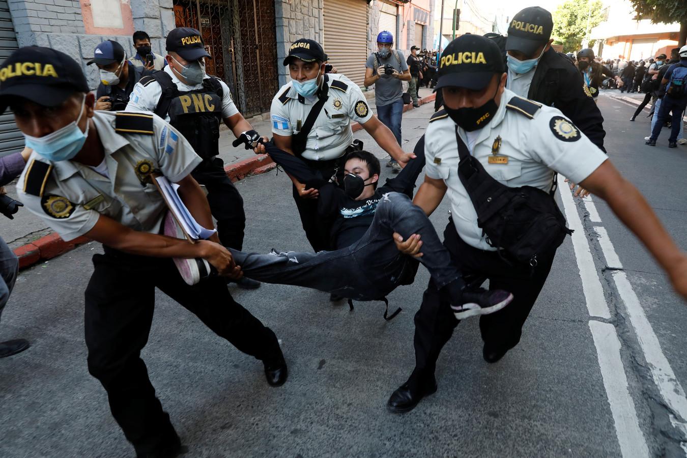 Politie-agenten voeren een betoger mee.
