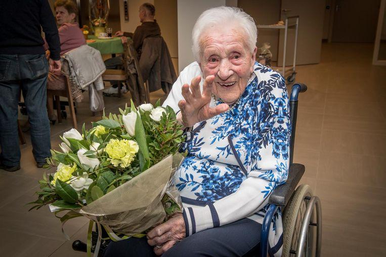 De jarige Hilda Declercq met een bos bloemen.