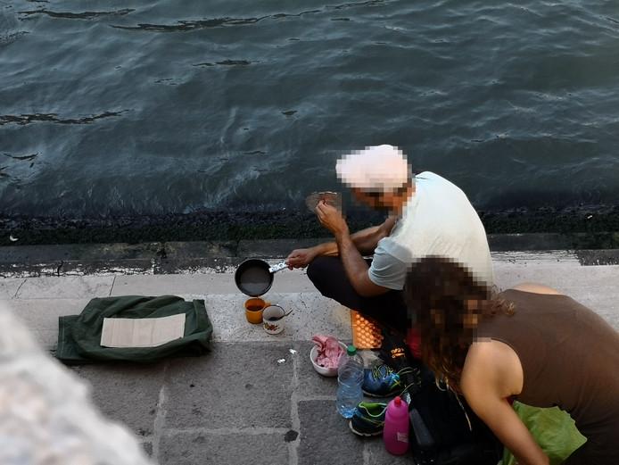 De twee Duitse toeristen zetten koffie aan de voet van de bekende Rialtobrug in Venetië.