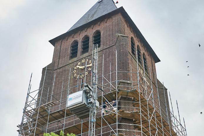 Medewerkers van het bedrijf Van Dinther uit Schaijk bouwen de steigers rond de kerktoren in Volkel.