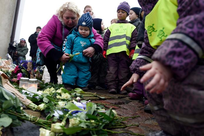 Een moeder legt samen met haar kind bloemen bij het koninklijk Paleis in het Deense Fredensborg, nadat de dood van Prins Henrik bekend is gemaakt. Foto Liselotte Sabroe