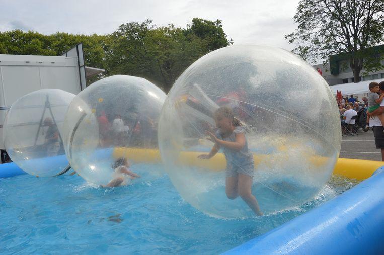 Kinderen maken pret met de waterballen op de kermis.