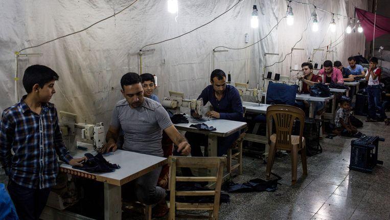 Syrische vluchtelingen die aan het werk zijn in een kledingbedrijf in Turkije.