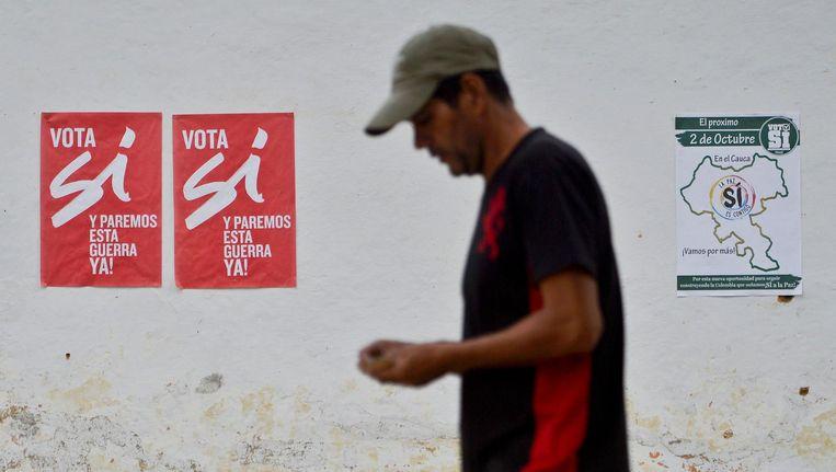 Een man loopt langs posters van het ja-kamp voor ratificatie van het vredesakkoord tussen de Colombiaanse regering en de FARC. Zondag verwierp de Colombiaanse bevolking het voorstel. Beeld anp