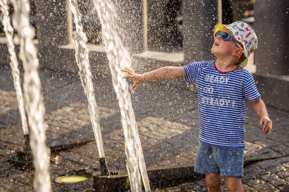 Een jongetje speelt in het water van de fontein op de Grote-Markt van Ieper tijdens de heetste dag ooit in België.