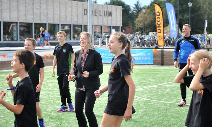Wethouder Marinka Mulder (midden) doet enthousiast mee tijdens een korfbalclinic op de open dag van Doelum.