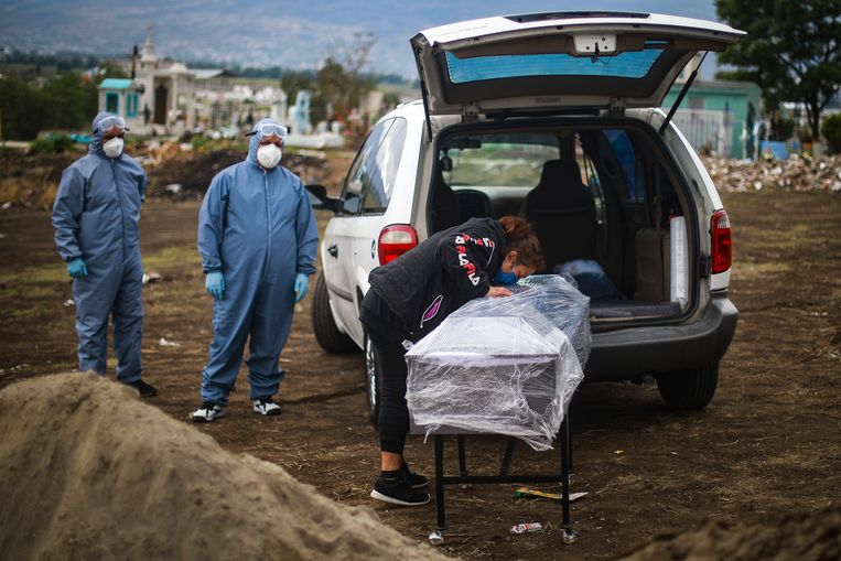 Een vrouw neemt afscheid van haar overleden familielid onder coronaomastandigheden in Valle de Chalco, Mexico.  Beeld Getty Images