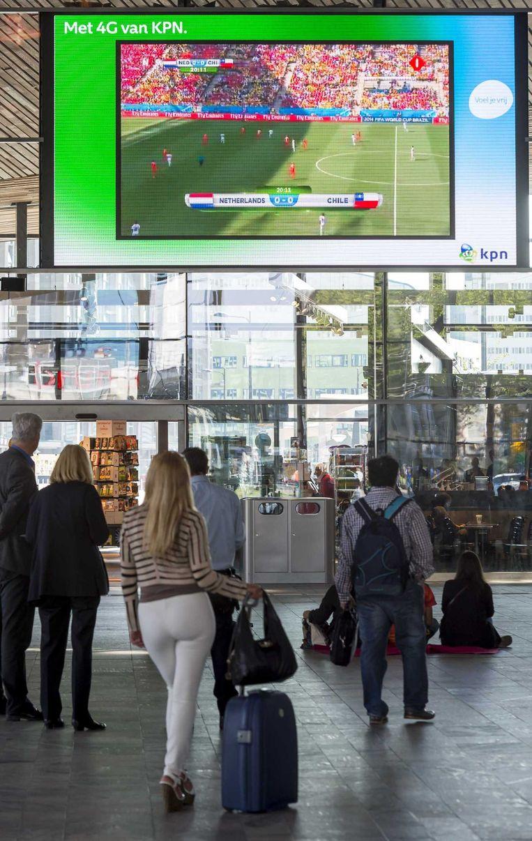 Treinreizigers kijken op een groot scherm in de centrale hal van treinstation Rotterdam Centraal naar de WK-wedstrijd tussen het Nederlands elftal en Chili. Beeld anp