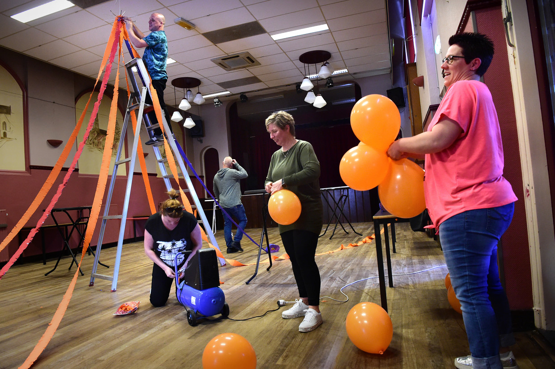 Oranje Vereniging Lepelstraat maakt zich op voor de Koningsnacht en de vrijwilligers maken het gemeenschapshuis gezellig. Beeld Marcel van den Bergh