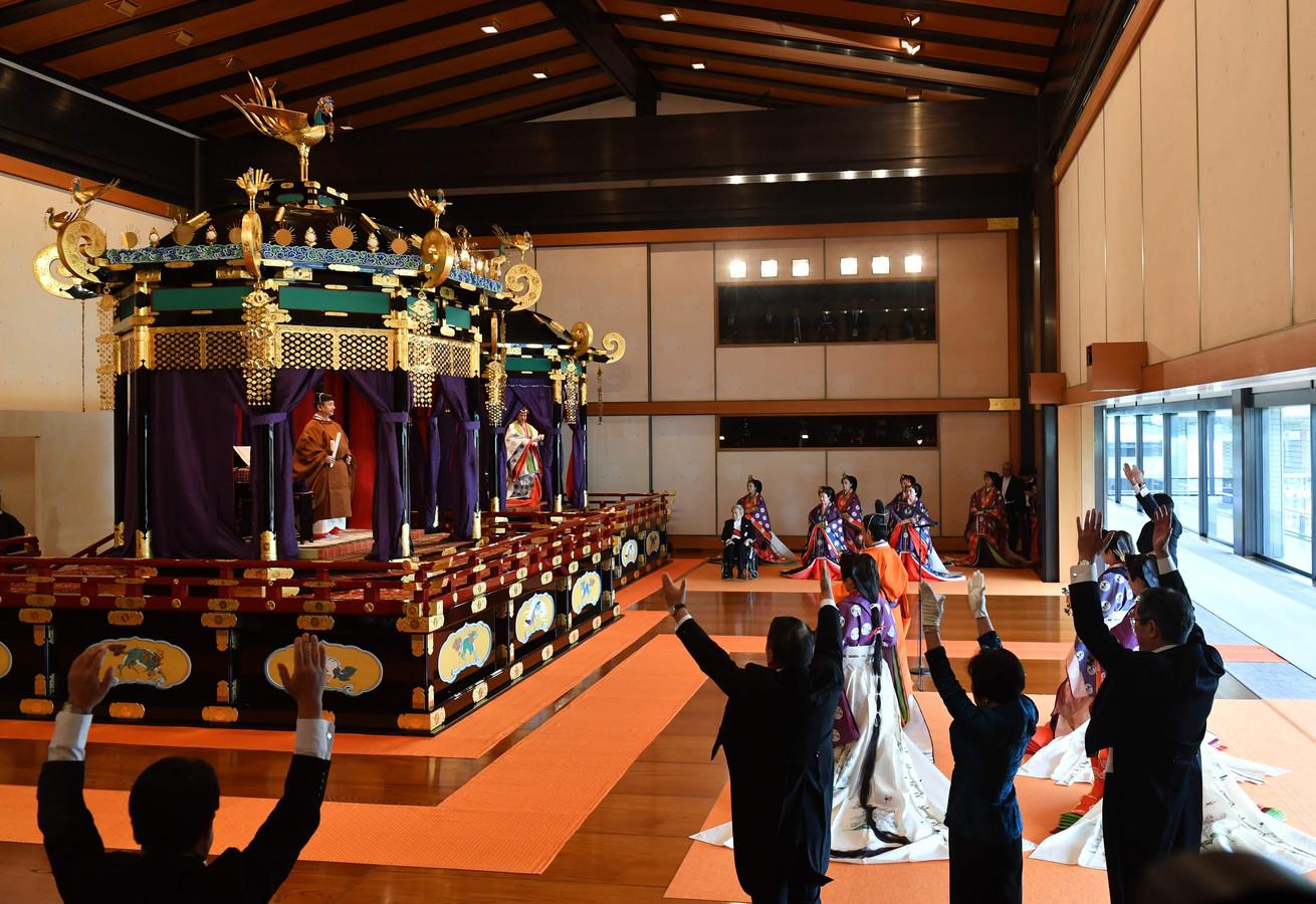 Banzai!, roepen de aanwezigen, onder wie de Japanse premier Abe (geheel rechts) voor de Japanse keizer Naruhito en zijn vrouw Masako tijdens de inhuldiging.