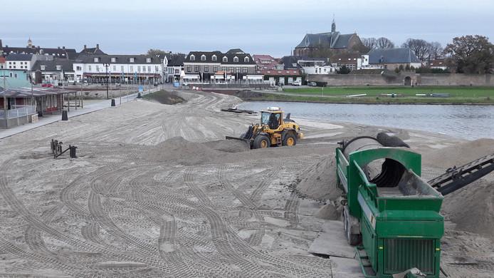 De toplaag van het strand wordt opzij geschoven om het schone zand er weer over te verspreiden.