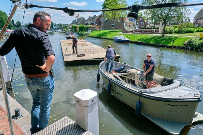 Horecamagnaat Bjorn van Dijl, met zonnebril op het bootje, vaart zelf het terrasvergrotende ponton naar Le Barrage in Alblasserdam. ,,Om het terras uit te breiden, konden we alleen het water op. Dus dat hebben we dan maar gedaan.
