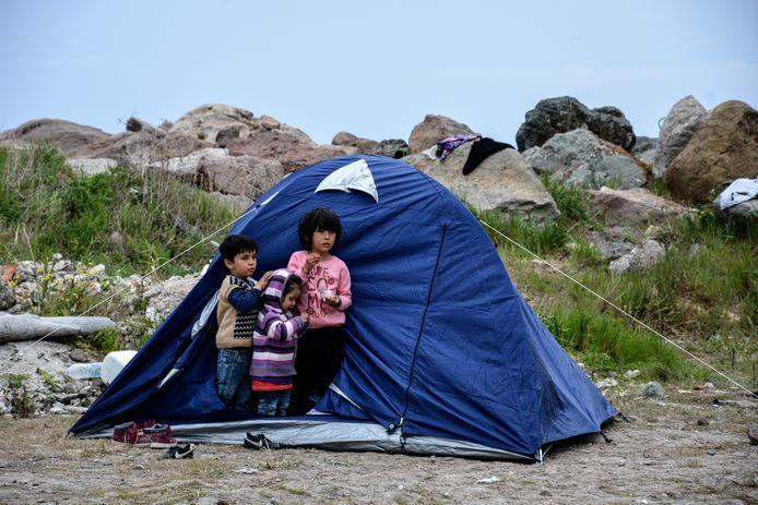 Kinderen staan in de opening van een tent op het Griekse eiland Lesbos.