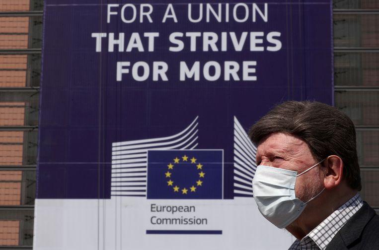 Een man met een mondkapje bij de Europese Commissie. Beeld Reuters