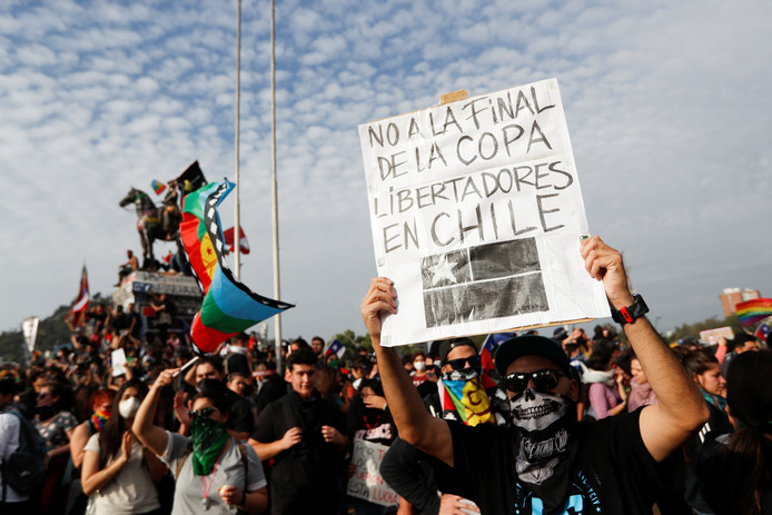 Een demonstrant houdt een plakkaat omhoog met de tekst 'Nee tegen de Copa Libertadores-finale in Chili', tijdens een protest tegen de Chileense regering in Santiago.