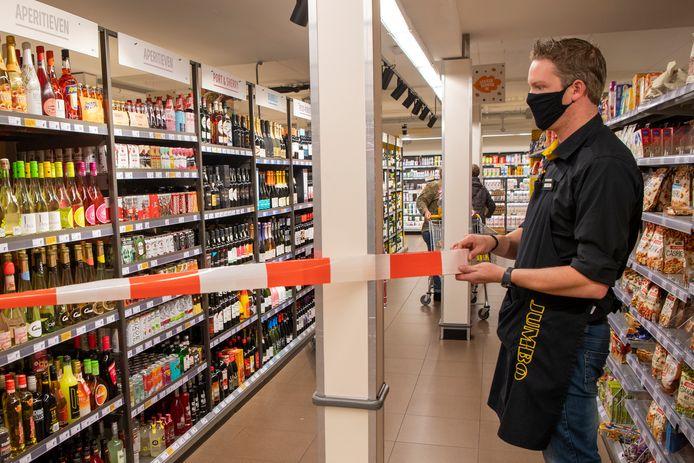 Jumbo Kamphuis in Dalfsen heeft ook met de strengere supermarkteisen te maken om het coronavirus in te dammen. Dat betekent na 20.00 uur geen alcoholverkoop meer. Jasper Posthumus spant een lint voor de drankstellage zodat klanten er niet meer bij kunnen.