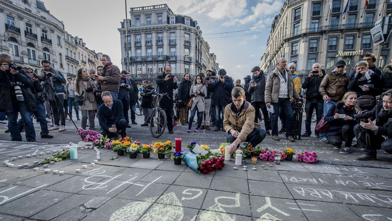 Op het Brusselse Beursplein worden met krijt leuzen en boodschappen van steun en liefde geschreven, bloemen neergelegd en kaarsen aangestoken. Hiermee tonen mensen hun solidariteit met de slachtoffers van de aanslagen in Brussel. Beeld anp
