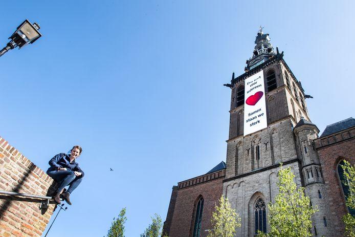 Julia Mulder met op de achtergrond de vlag met het rode hart die wappert vanaf de Stevenskerk.