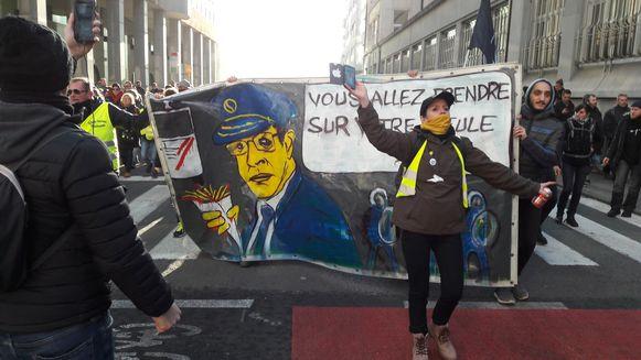 De betogers bij het spandoek waarmee commissaris Vandersmissen op de korrel genomen wordt.