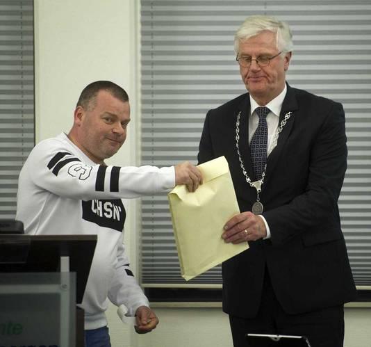 Inwoner Danker Kouwen (L) overhandigt handtekeningen voor een referendum aan burgemeester Joseph Vos tijdens de raadsvergadering.