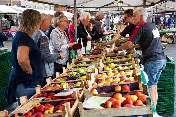 Drukte bij de fruit- en sappenkraam van de familie Smorenburg op de streekmarkt in Woerden. Leen en Marrie Pauw (tweede en derde van links) gaan elke zaterdag, dus ook vanmorgen.