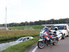 Auto te water in Woerden; man haalt nat pak