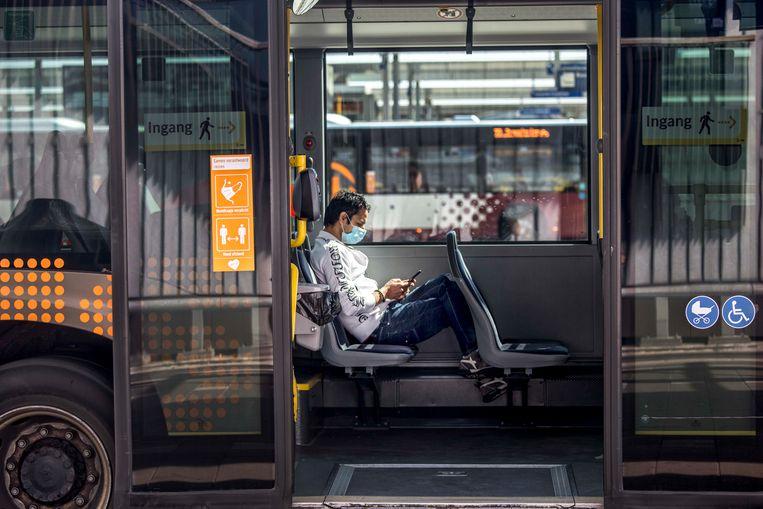 Een man met een mondkapje in de bus in Utrecht. Beeld Raymond Rutting / de Volkskrant