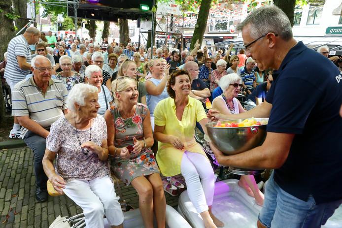 Marco Uijterlinde deelt ijsjes uit aan Pietje Rijkers, Lijda de Kock en Elly de Ruiter op het bankje vooraan.