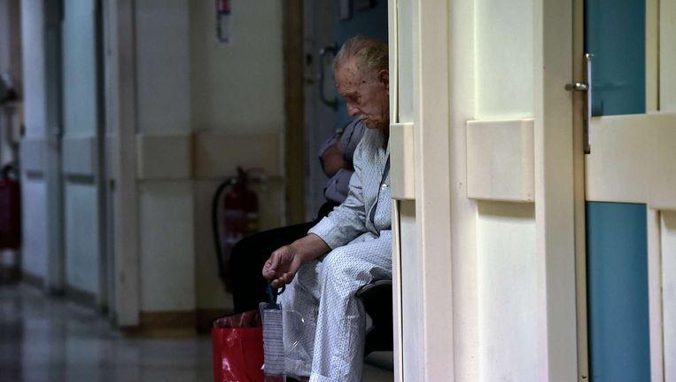 Een patiënt zit op de gang in een ziekenhuis in Athene. Beeld afp