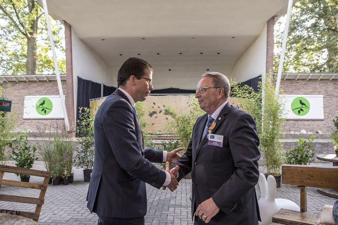Burgemeester Joost van Oostrum van Berkelland feliciteert Rinus Smet na zijn huldiging waarbij de Borculoër Ridder in de Orde van Oranje Nassau is geworden.