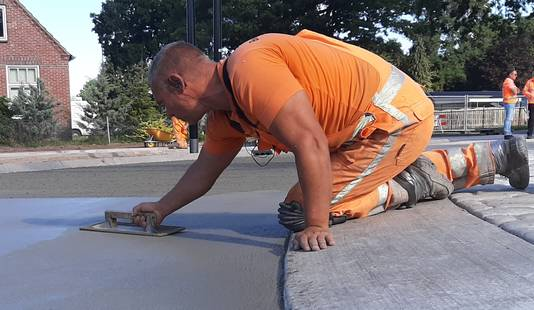 Een werknemer van Wetering schuurt het beton plat en glad. Hierna trekt een collega er nog dwarsstrepen over om te voorkomen dat het wegdek té glad wordt.