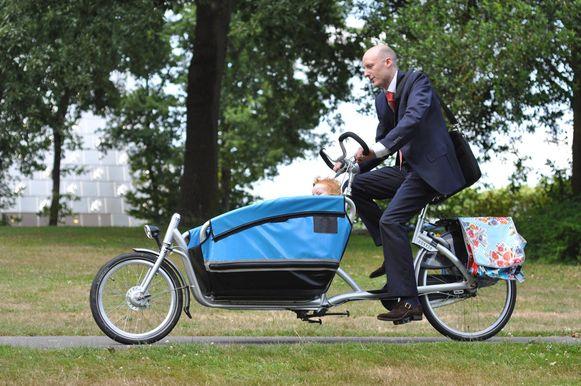 Een zakenman brengt zijn kind eerst per fiets naar de crèche.