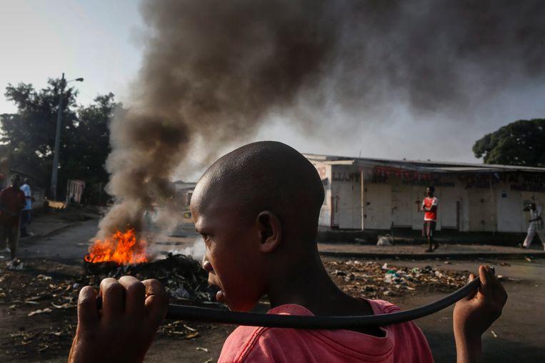 Een jongen kijkt om zich heen, met voor zich een brandende barricade, tijdens een anti-regeringsdemonstratie tegen Burundi's president Pierre Nkurunziza. Beeld epa
