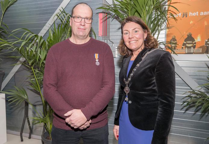 Mart Potter (links) met zijn onderscheiding die hij kreeg opgespeld door burgemeester José van Egmond (rechts).