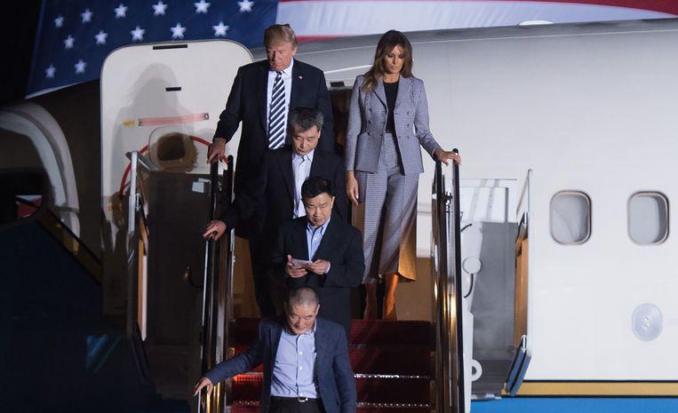 Donald Trump en zijn vrouw Melania dalen de vliegtuigtrap af achter de vrijgelaten Tony Kim (bovenaan de trap), Kim Dong-chul (beneden) en Kim Hak-song (midden) Beeld null