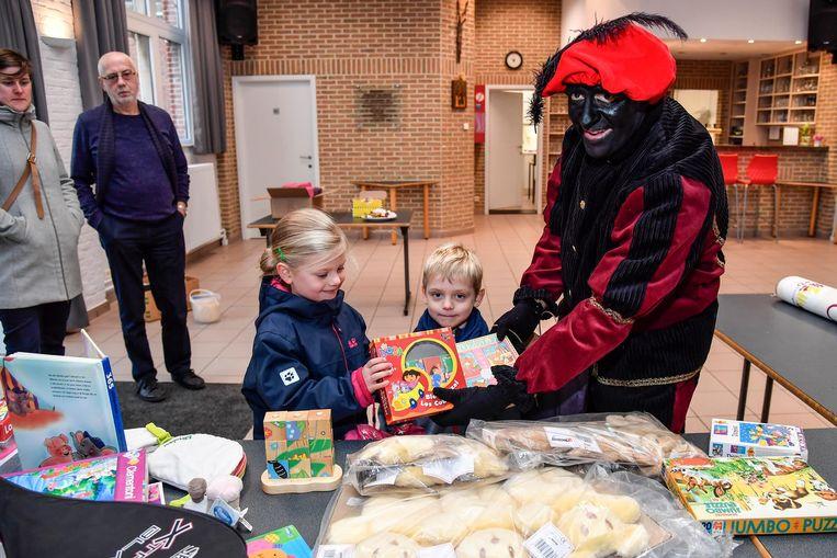 Enkele kinderen brengen hun oud speelgoed naar Zwarte Piet.