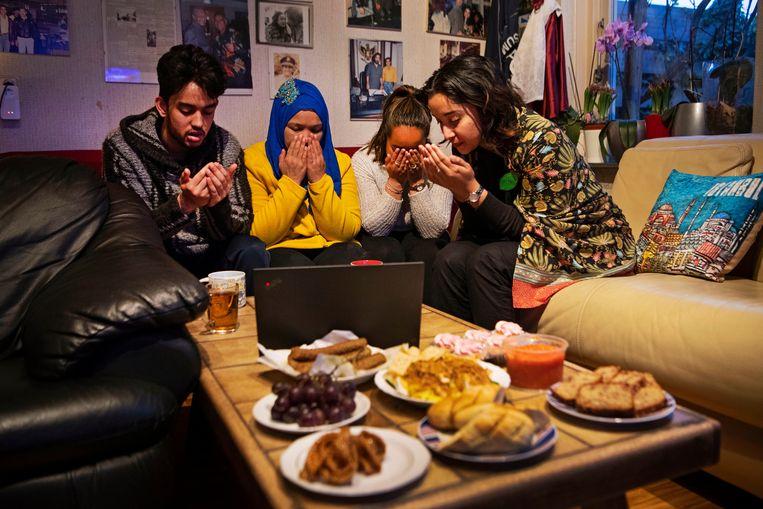 Dimple Sokartara (R), haar moeder, zusje en broertje, bidden voor de Iftarmaaltijd. Via Zoom zijn er nog meer mensen virtueel aanwezig bij het verbreken van het vasten. Beeld Olaf Kraak