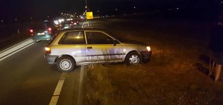 Auto rijdt zich vast op betonband bij keren op de weg