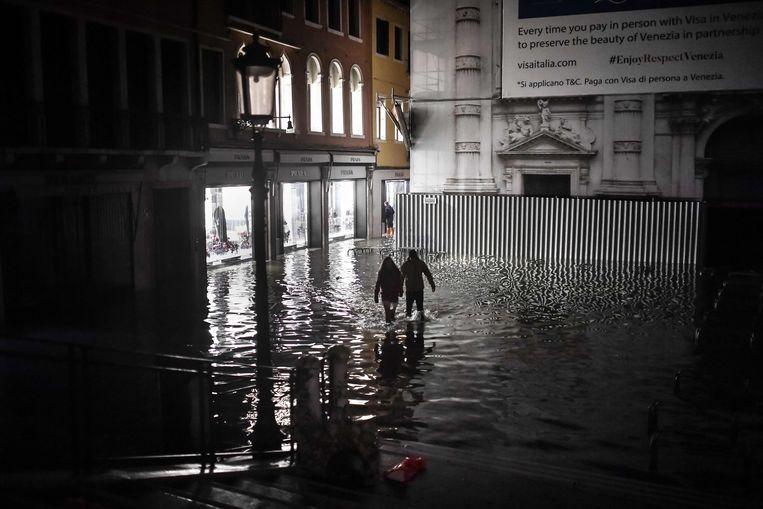 Mensen waden door het water in Venetië.