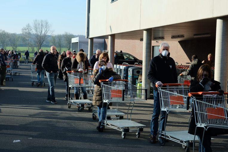 Klanten staan met mondmaskers aan te schuiven voor de ingang van het Colruyt-warenhuis in Nossegem.