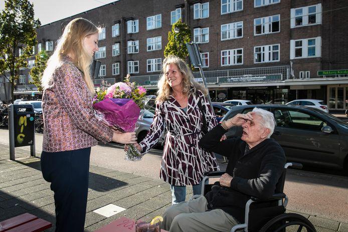 Lizzy Aukes neemt de bloemen in ontvangst die Henk Brenker en zijn dochter Rina hebben meegenomen.
