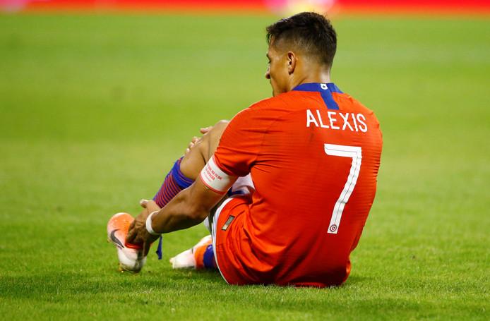 Alexis grijpt naar zijn pijnlijke enkel.