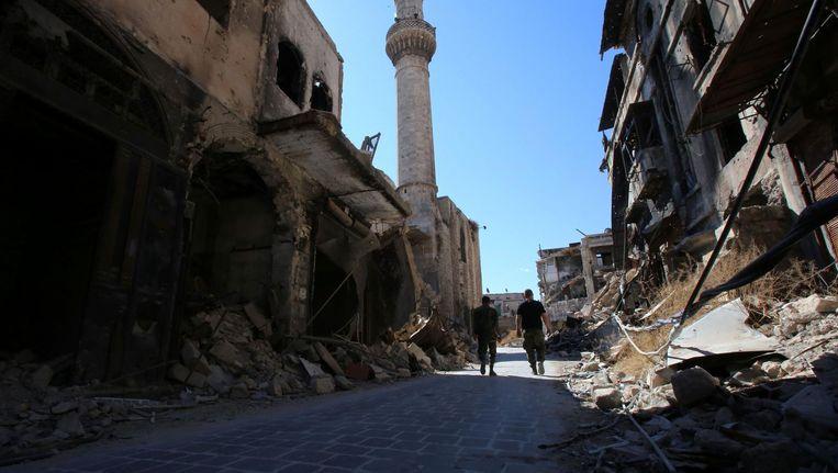 Syrische regeringssoldaten lopen door de verwoeste oude souk in de noordelijke stad Aleppo. Beeld afp