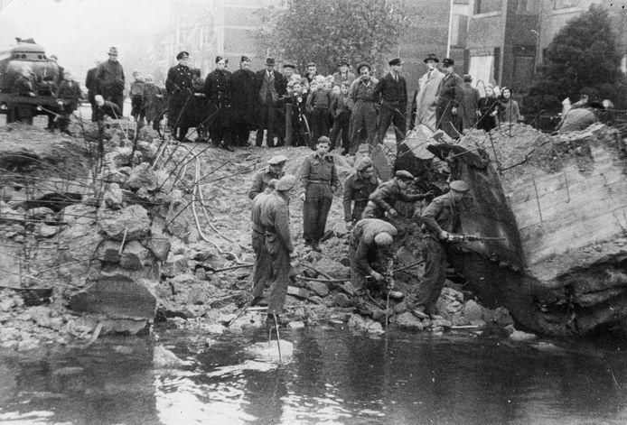 Britse militairen staan tussen de resten van de Vaartbrug die op 6 mei 1945 in Veenendaal werd opgeblazen. Op de achtergrond kijken tientallen nieuwsgierige burgers toe.