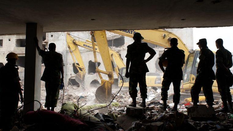 Reddingswerkers in het puin van de ingestorte fabriek. Beeld epa